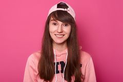 Beautiful charming girl wears pink hoodie and visor cap back. Young lady has dark long hair, has fantastic mood, going out with. Friends, stands smiling  over stock images