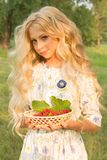 Beautiful charming long curly blonde hair teenage girl wearing a. Long light dress outdoors on a picnic holds a plate full of raspberries in her hands. Copy Royalty Free Stock Photos
