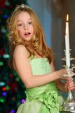 Beautiful charming pretty blond child-girl on the background of a New Year tree. Beautiful charming pretty blond child-girl in a festive green dress with Stock Images