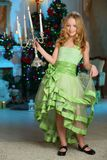 Beautiful charming pretty blond child-girl on the background of a New Year tree. Beautiful charming pretty blond child-girl in a festive green dress with Stock Image
