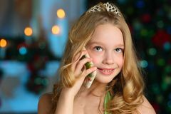 Beautiful charming pretty blond child-girl on the background of a New Year tree. Beautiful charming pretty blond child-girl in a festive green dress on the Stock Images