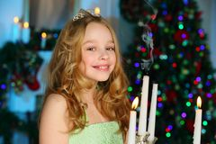 Beautiful charming pretty blond child-girl on the background of a New Year tree. Beautiful charming pretty blond child-girl in a festive green dress with Royalty Free Stock Images