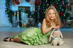 Pretty blond child-girl on the background of a New Year tree. Beautiful charming pretty blond child-girl in a green dress with her favorite toy on the background Royalty Free Stock Photography