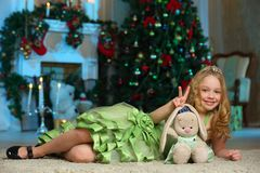 Pretty blond child-girl on the background of a New Year tree Royalty Free Stock Image