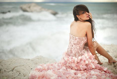 Beautiful, charming and sexy woman, model sitting on rocks, clif. Fs during sunset. Windy day at paradise Royalty Free Stock Photography