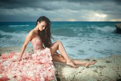 Beautiful, charming and sexy woman, model sitting on rocks, clif. Fs during sunset. Windy day at paradise Royalty Free Stock Image