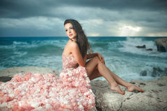 Beautiful, charming and sexy woman, model sitting on rocks, clif. Fs during sunset. Windy day at paradise Stock Photo