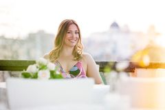 Beautiful and charming smiling woman sitting outdoor. Looking with positive and joyful attitude. Blurred background stock photography