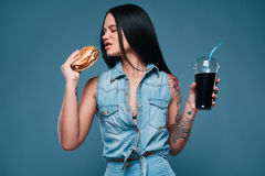 Beautiful charming tattoo girl with hamburger and soda. Glamorous fashion portrait of beautiful charming tattoo girl with hamburger and soda on a bright royalty free stock photography