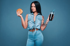 Beautiful charming tattoo girl with hamburger and soda. Glamorous fashion portrait of beautiful charming tattoo girl with hamburger and soda on a bright royalty free stock photos