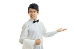 Beautiful charming waiter in a white shirt smiles and holds out his hand toward the Stock Photo