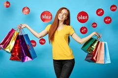 Beautiful charming woman with closed eyes holding shopping bags stock image