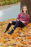 Beautiful charming young attractive girl with large blue eyes, with long dark hair in the autumn forest sits on the leaves near th Royalty Free Stock Images