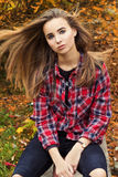 Beautiful charming young attractive girl with large blue eyes, with long dark hair in the autumn forest sits on a tree in black stock photography