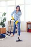 Beautiful charwoman cleaning with vacuum cleaner carpet. Mid shot of beautiful charwoman cleaning with vacuum cleaner carpet stock images