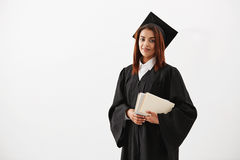 Beautiful cheerful african female graduate smiling holding books looking at camera. Copy space. royalty free stock images