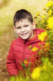 Beautiful and cheerful boy with flowers. Royalty Free Stock Photos