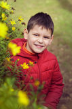 Beautiful and cheerful boy with flowers. Stock Photos