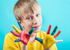 Beautiful cheerful boy in yellow t-shirt showing painted hands Stock Photography