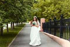 Beautiful cheerful bride in a white dress and veil with a bouquet in her hands looking at the camera in the Park in full length su royalty free stock photo