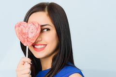 Brunette girl dressed in blue smiling, closing her eye with heart shaped red candy like a mask. Saint Valentine`s Day concept. Beautiful cheerful brunette girl royalty free stock images