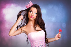 Beautiful cheerful brunette girl in a pink dress and pink crown on his head holding a lollipop. Mini with sequins and feathers. long hair. gray background Stock Photos