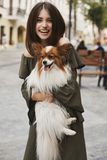 Beautiful and cheerful brunette model girl with shiny smile, in short dress with a small cute papillon dog on her hands posing out royalty free stock image