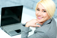 Beautiful cheerful businesswoman sitting at her workplace Stock Photos