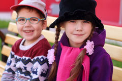 Beautiful cheerful children, boy and girl in bright clothes sitt Stock Photos