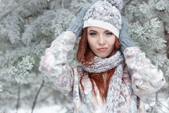 Beautiful cheerful cute red-haired girl in a cap and scarf plays with snow in the beautiful forest fairy Royalty Free Stock Photo