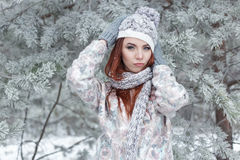 Beautiful cheerful cute red-haired girl in a cap and scarf plays with snow in the beautiful forest fairy Royalty Free Stock Images