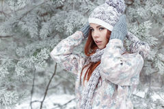 Beautiful cheerful cute red-haired girl in a cap and scarf plays with snow in the beautiful forest fairy Royalty Free Stock Photos