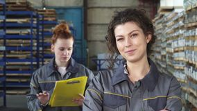 Beautiful cheerful female factory worker smiling to the camera