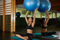 Beautiful cheerful girl begins his training with exercises with fitball. Young athletic woman holding up Pilates ball and sitting on the mat during her fitness Stock Photos