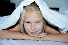 Beautiful cheerful girl looks out from under a. Beautiful cheerful girl looks out from under white  blanket Royalty Free Stock Photo