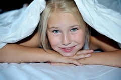 Beautiful cheerful girl looks out from under a. Beautiful cheerful girl looks out from under white  blanket Stock Images
