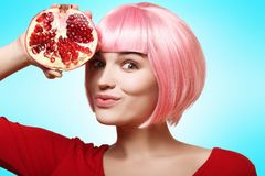Beautiful and cheerful girl in a pink wig and red clothes is holding a fruit of pomegranate in her hand, on colored background Stock Photos