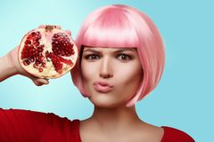 Beautiful and cheerful girl in a pink wig and red clothes is holding a fruit of pomegranate in her hand, on colored background Royalty Free Stock Images