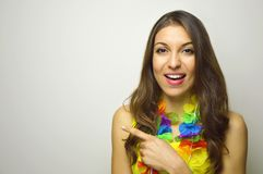 Beautiful cheerful girl ready for carnival party pointing your product or text on gray background. Royalty Free Stock Photography