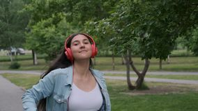 Beautiful cheerful girl in red headphones walks down the street and dances listening music. Beautiful cheerful girl in red headphones walks down the street in stock video footage