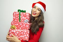 Beautiful cheerful girl with Santa Claus hat holdings her christmas presents on white background.  Stock Image