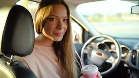 Beautiful cheerful girl sits in the car, drinks coffee and laughs stock video footage