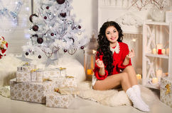 Beautiful cheerful girl sitting on the floor by the fireplace wi. Th a sparkler. Christmas tree and presents Stock Photos