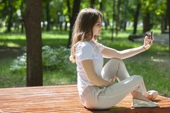 Beautiful cheerful girl with a smartphone sitting in a park on a bench on a sunny day royalty free stock photography