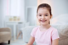 Beautiful cheerful girl smiling to camera. Sincere smile. Positive energetic nice girl grinning whole staring at camera and posing on blurred background Royalty Free Stock Image