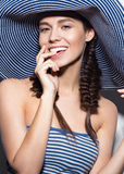 Beautiful cheerful girl in a summer beach striped hat. The beauty of the face. Royalty Free Stock Photos