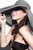 Beautiful cheerful girl in a summer beach striped hat. The beauty of the face. Royalty Free Stock Photography
