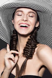 Beautiful cheerful girl in a summer beach striped hat. The beauty of the face. Royalty Free Stock Image