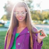 Beautiful cheerful girl with a sweet smile in sunglasses. And a bright colorful jacket on a sunny day stock image