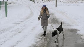 Beautiful cheerful girl walking the dog Pointer in the snow.